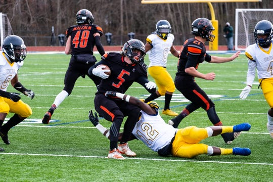 Almont's Jack Paupert is tackled by Detroit Denby's Karl Foster as he runs with the football in the MHSAA Division 5 state semifinal Saturday, Nov. 23, 2019, at Walled Lake Central.