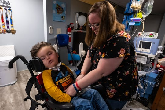 Jamie Welser works to get her son Ben, 5, into his chair Saturday, Nov. 23, 2019, in the basement of her Marysville home.