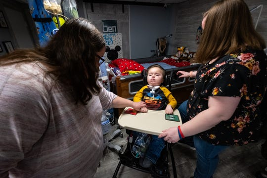Jamie Welser, right, works with her mother Laura Welser, left, to get her son Ben, 5, into his chair Saturday, Nov. 23, 2019, in the basement of her Marysville home.
