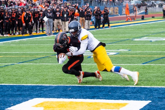 Almont's Jack Paupert is tackled inside the end zone by Detroit Denby's Keyon Hammond, giving Almont their first touchdown in the MHSAA Division 5 state semifinal Saturday, Nov. 23, 2019, at Walled Lake Central.