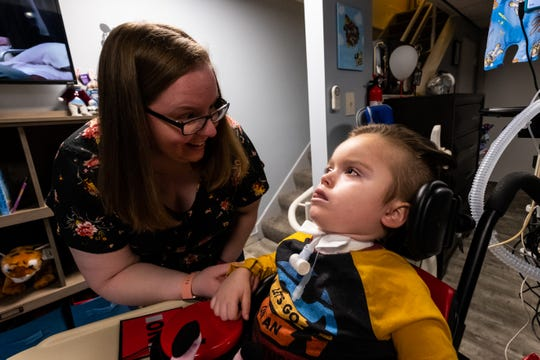 Jamie Welser tries to get her son Ben, 5, to smile Saturday, Nov. 23, 2019, in the basement of her Marysville home. Ben recently returned home after almost five months in the hospital.