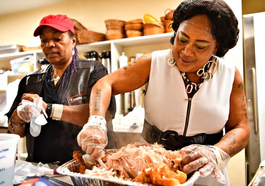Vendettia Banks, left, of York City, prepares to help Tonya Larry carve a turkey during Thanksgiving Community Dinner, provided by The Movement and Elite Property Management, at Union Lutheran Church in York City, Saturday, Nov. 23, 2019. Dawn J. Sagert photo