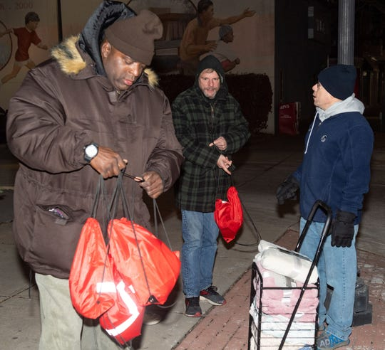 From left, Shawn Jamison, York Mayor Michael Helfrich and Clinton Hayes walk the streets looking for people to hand blankets and other essentials to during the York City Community Coordinators' Homelessness Awareness Walk.