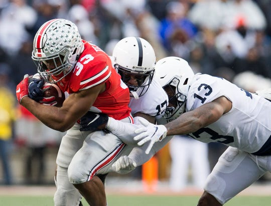 Nov 23, 2019; Columbus, OH, USA; Ohio State Buckeyes running back Master Teague III (33) tries to evade a tackle attempted by Penn State Nittany Lions safety Garrett Taylor (17) and linebacker Ellis Brooks (13) in the second half at Ohio Stadium. Mandatory Credit: Greg Bartram-USA TODAY Sports