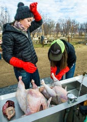 Aspen Wright wipes her forehead while taking a break from cleaning turkeys.