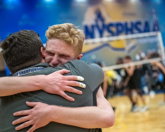 McQuaid Jesuit senior Owen Wickens hugs one of his coaches after beating Sachem North to win the New York State Division I Boys Volleyball Championship at the Capital Center in Albany New York on Saturday, Nov. 23, 2019