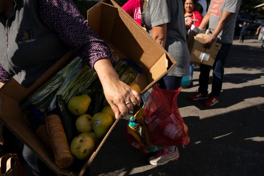 Families carry boxes full of fresh produce during a food bank event at El Verano elementary on November 1, 2019. The school typically hosts about 50 families at their weekly food bank but saw more than twice that number when they opened the event to the entire community following a week of public safety power outages that caused many to lose their fresh food. Photo by Anne Wernikoff for CalMatters