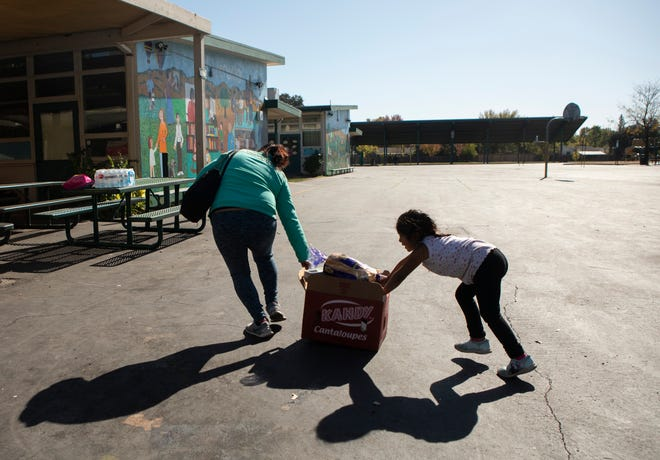 Romy Hernandez and her daughter push a heavy crate full of food across the El Verano Elementary yard during the school's food bank on November 1, 2019 following a week of public safety power outages that caused Hernandez to lose all the food in her fridge. The school hosts a weekly food bank for families of students but opened the event to the entire community this week. Photo by Anne Wernikoff for CalMatters