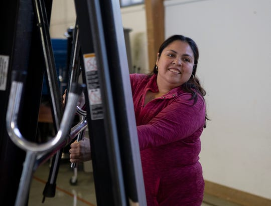 El Verano elementary parent and food bank volunteer Ana Rios puts away folding tables in the school cafeteria after the food pantry.