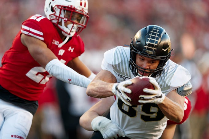Nov 23, 2019; Madison, WI, USA; Purdue Boilermakers tight end Brycen Hopkins (89) dives to score a touchdown in front of Wisconsin Badgers cornerback Caesar Williams (21) and linebacker Jack Sanborn (57) during the second quarter at Camp Randall Stadium. Mandatory Credit: Jeff Hanisch-USA TODAY Sports