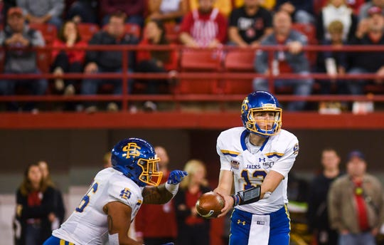 SDSU quarterback Keaton Heide (13) hands off the ball to SDSU running back Mikey Daniel (26) during the game against USD on Saturday, Nov. 23, 2019, at the DakotaDome in Vermillion.
