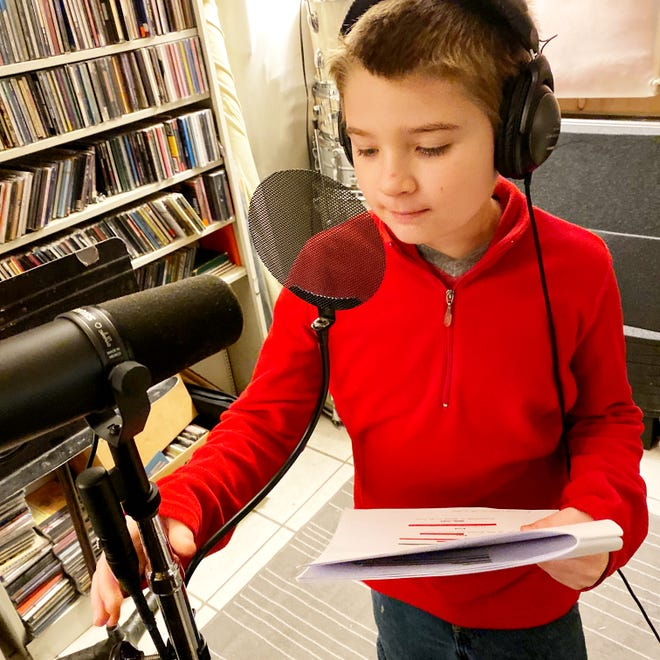 Toby Kinsinger leans in to the mic while providing the voice for a cartoon goat.
