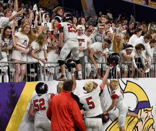 ROCORI senior captain Isaac Massmann climbs into the student section after the Spartans advanced to the Prep Bowl Friday, Nov. 15, 2019, at U.S. Bank Stadium.