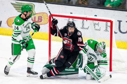 St. Cloud State forward Sam Hentges falls into Fighting Hawks goalie Adam Scheel's (31) crease late in the first period of Friday's hockey matchup at Ralph Engelstad Arena.