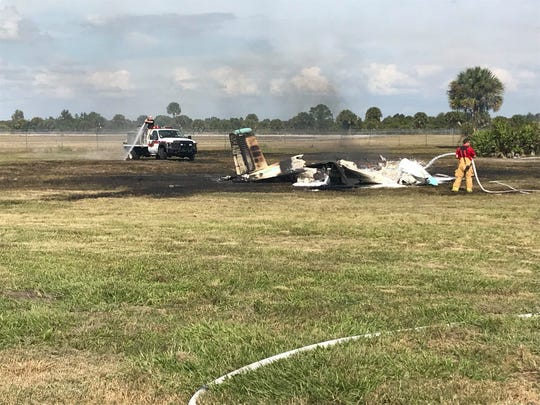 A firefighter douses the charred wreckage of a single-engine Piper plane that crashed Saturday near the Okeechobee County Airport on November 23, 2019. Three people were injured.