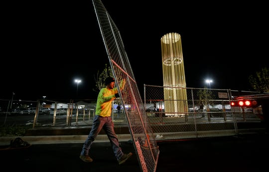 """Workers with National Construction Rentals remove the chain link fencing around the """"Grand Candela"""" at Walmart on Friday night, Nov. 23, 2019, after it was lit for the first time. It serves as a memorial to the 22 people killed in the mass shooting at the East El Paso store Aug. 3."""