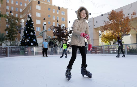 Emily Sheldon, 9, smiles as she glides around the skating rink at WinterFest on Saturday, Nov. 23, 2019, in Downtown El Paso. The winter festival kicked off Saturday.