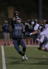 Camarillo High quarterback James McNamara has to get rid to the ball quickly as Loyola's Blake Neithart and Jeffrey Johnson close in during their CIF-SS Division 4 semifinal game Friday night at Moorpark College. Camarillo lost, 31-14.