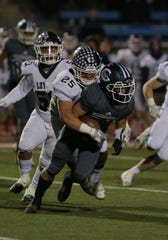 Camarillo High's Tyler Macasieb can't shake off Loyola's Steven Arellano during the first quarter of Friday night's CIF-SS Division 4 semifinal game at Moorpark College. Camarillo lost, 31-14.