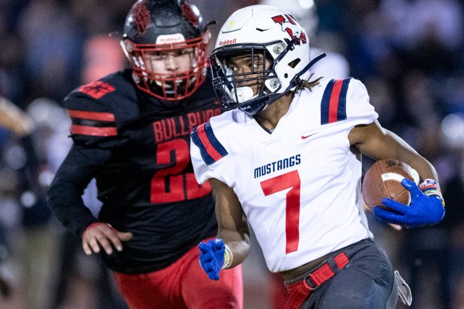 Tulare Western's Tairyn Johnson runs ahead of Hanford's Garrett Revious in a Central Section Division II semifinal football game on Friday, November 22, 2019.