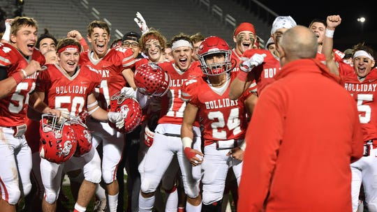 Holliday Eagles players anticipate coach Frank Johnson handing them the trophy after winning the 3A Division II Area playoff game againnst Palmer Friday night in Mineral Wells.