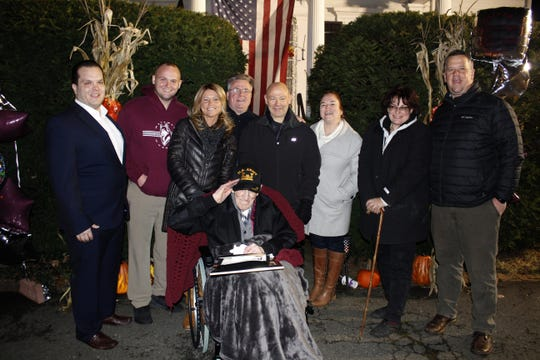 Surrounded by Matawan borough officials outside his home (plus daughter Deborah, second from right), Howard Lloyd salutes on his 100th birthday.