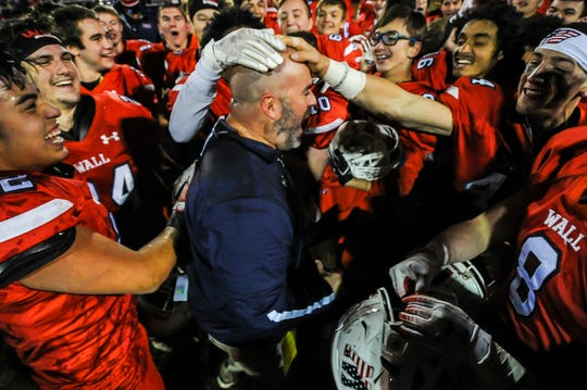 Wall head coach Tony Grandinetti (middle) celebrates with his players after the Crimson Knights won the NJSIAA Central Group III championship this past Friday night with a 14-13 win over Rumson-Fair Haven.