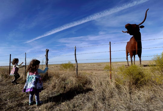"""Willow and Lilybelle Erdrich react to Joe Barrington's """"Bridle Bit Bull"""" sculpture on U.S. 380 in Oct. 2015. The 22-foot tall steel longhorn sits on private land, but still lends itself as a fun place for quirky roadside pictures along the fence."""