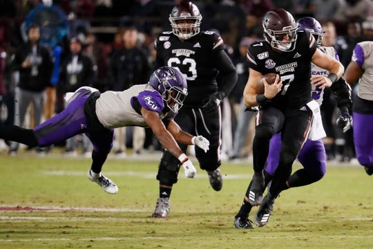 Mississippi State quarterback Tommy Stevens (7) evades an Abilene Christian defender as he runs for short yardage during the first half Saturday, Nov. 23, 2019, in Starkville, Miss.