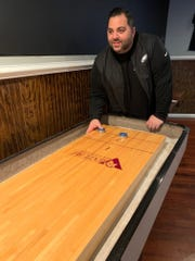 General Manger Jonathan Crugnale of  Southampton plays shuffleboard at the White Horse Pub in Oaklyn.