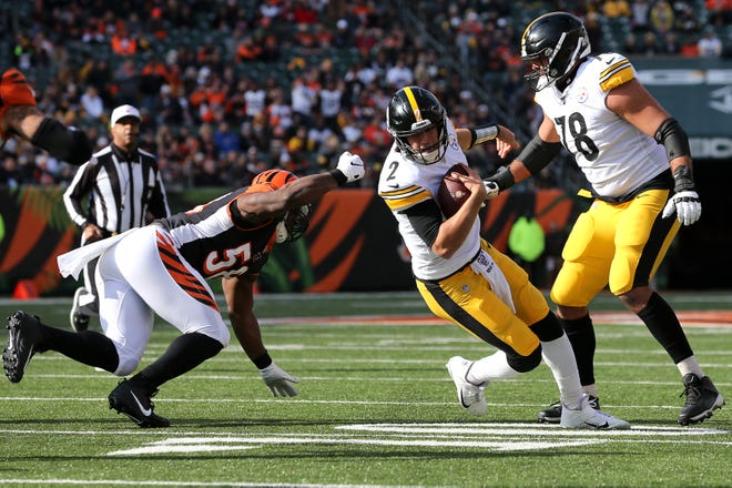 Pittsburgh Steelers quarterback Mason Rudolph (2) spins out of an arm tackle by Cincinnati Bengals defensive end Carl Lawson (58) in the first quarter of an NFL Week 12 game, Sunday, Nov. 24, 2019, at Paul Brown Stadium in Cincinnati.