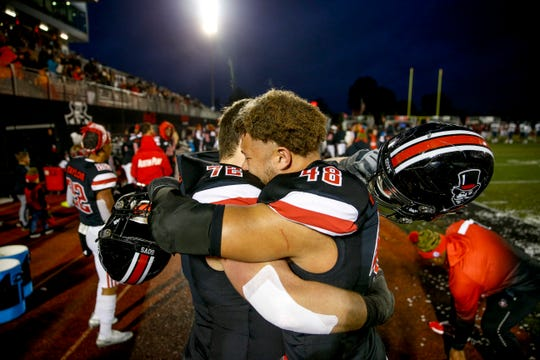 Austin Peay defensive lineman Shaun Whittinghill (48) and offensive lineman Hunter Schmeisser (72) hug after realizing the Govs won the OVC co-championship Saturday.