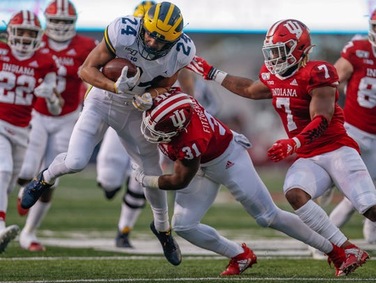 BLOOMINGTON, IN - NOVEMBER 23: Zach Charbonnet #24 of the Michigan Wolverines is tackled by Bryant Fitzgerald #31 of the Indiana Hoosiers during the first half at Memorial Stadium on November 23, 2019 in Bloomington, Indiana. (Photo by Michael Hickey/Getty Images)