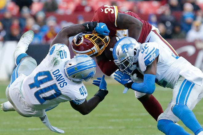 Washington Redskins running back Wendell Smallwood is tackled by Detroit Lions linebacker Jarrad Davis and safety Tavon Wilson in the fourth quarter at FedExField, Nov. 24, 2019.