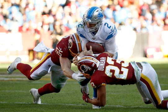 Lions quarterback Jeff Driskel is tackled by Washington linebacker Cole Holcomb, left, and cornerback Quinton Dunbar during the first half on Sunday, Nov. 24, 2019, in Landover, Md.