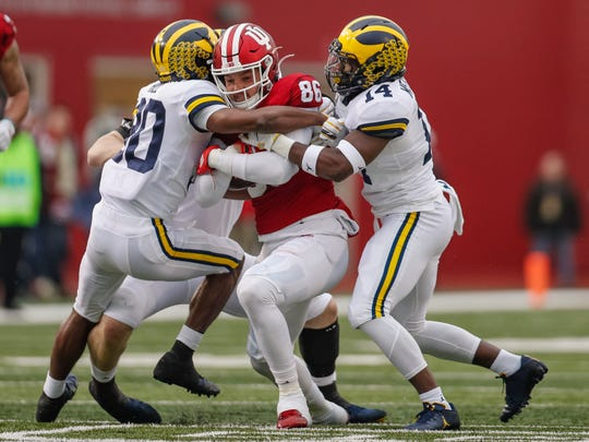 BLOOMINGTON, IN - NOVEMBER 23: Peyton Hendershot #86 of the Indiana Hoosiers runs the ball after a reception as Daxton Hill #30 of the Michigan Wolverines and Josh Metellus #14 of the Michigan Wolverines make the stop during the first half at Memorial Stadium on November 23, 2019 in Bloomington, Indiana. (Photo by Michael Hickey/Getty Images)