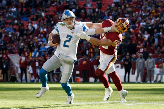 Lions quarterback Jeff Driskel stiff arms Washington linebacker Cole Holcomb during the first half on Sunday, Nov. 24, 2019, in Landover, Md.