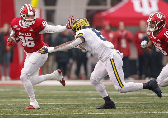 Indiana's Peyton Hendershot tries to avoid Michigan's Josh Uche during the first half Nov. 23, 2019 in Bloomington, Ind.