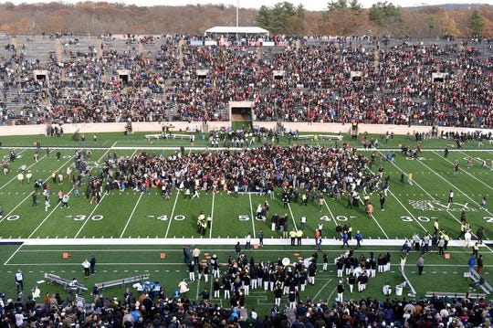 Demonstrators stage a climate change protest at the Yale Bowl delaying the start of the second half of an NCAA college football game between Harvard and Yale Saturday, Nov. 23, 2019, in in New Haven, Conn.