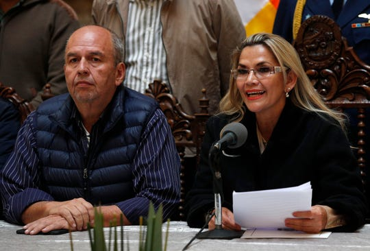 Accompanied by Government Minister Arturo Murillo, Bolivia's interim President Jeanine Anez speaks during a press conference at the presidential palace, in La Paz, Bolivia, Saturday, Nov. 23, 2019.