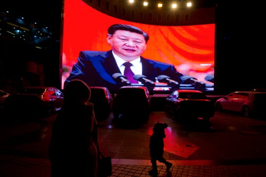A child walks past a large screen showing Chinese President Xi Jinping near a carpark in Kashgar, western China's Xinjiang region on Dec. 3, 2018.