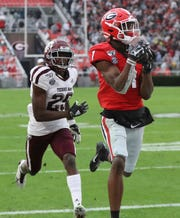 Georgia wide receiver George Pickens (1) makes a catch for a touchdown as Texas A&M defensive back Debione Renfro (29) defends in the first half.
