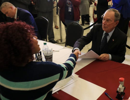 Raynetta Hansberry (left), election coordinator with the Secretary of State's office, shakes hands with former New York City Mayor Michael Bloomberg as he files paperwork, Tuesday, Nov. 12, 2019, at the state Capitol in Little Rock, Ark., to appear on the ballot in Arkansas' March 3 presidential primary.