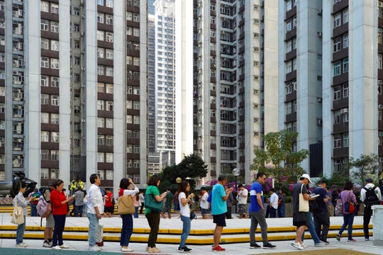 People line up to vote outside of a polling place in Hong Kong, Sunday, Nov. 24, 2019.