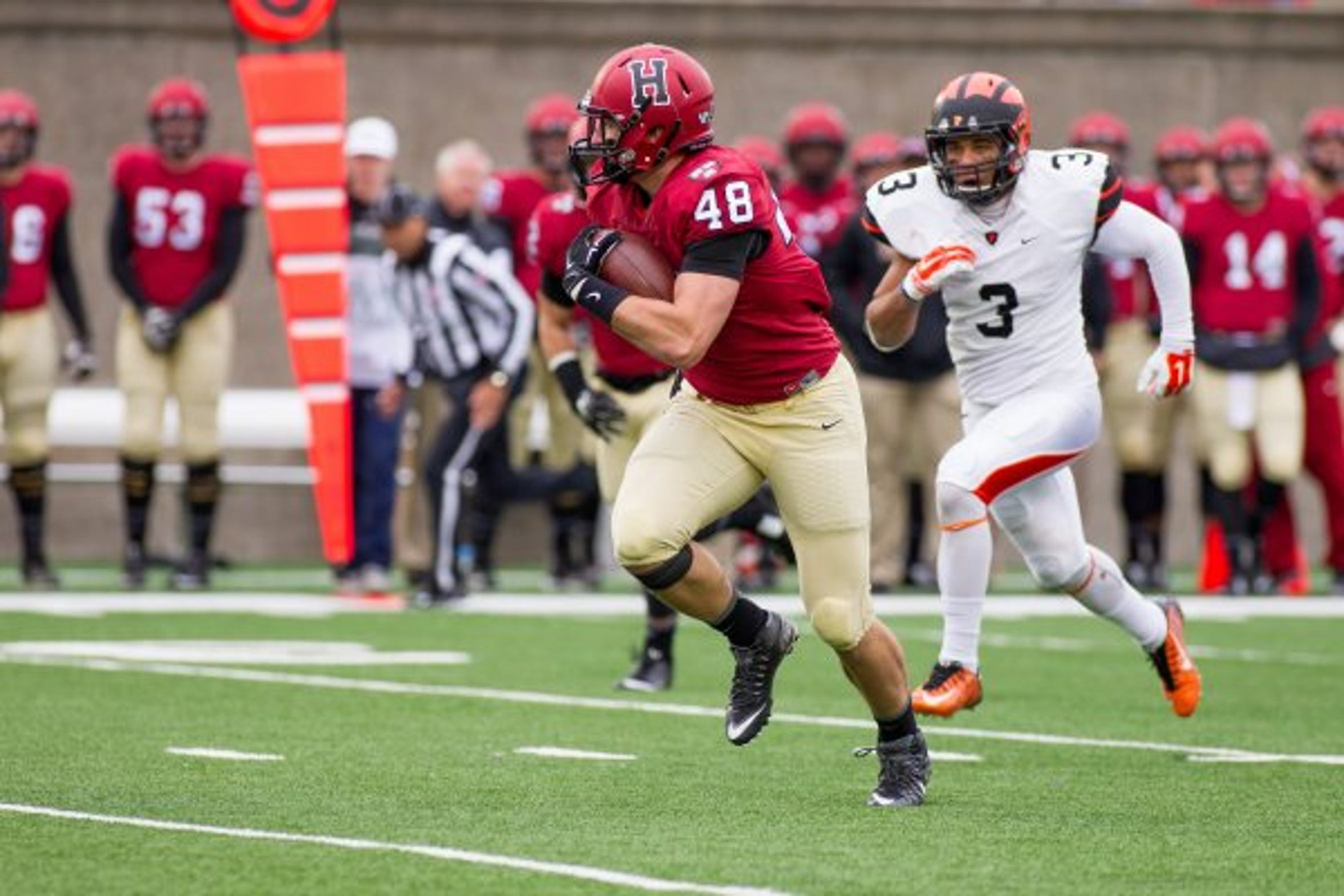 Ben Braunecker runs after catching a pass during his time with the Harvard Crimson.