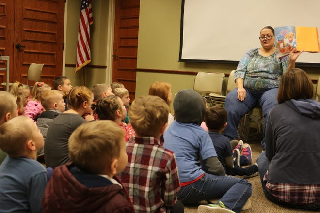 Deb Meyer reads a gingerbread man story at the Clyde Public Library on Saturday as part of the Winesburg Christmas Weekend.