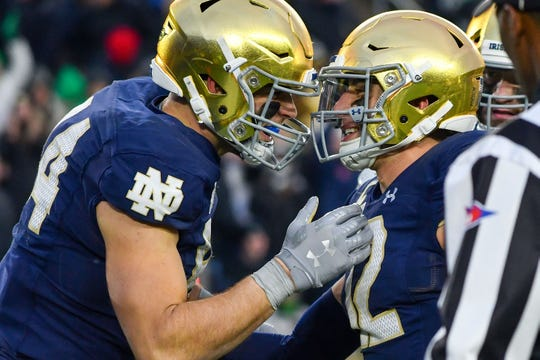 Notre Dame Fighting Irish tight end Cole Kmet (84) celebrates with quarterback Ian Book (12) after a touchdown catch in the third quarter against the Boston College Eagles at Notre Dame Stadium.