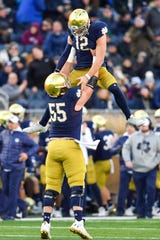 Notre Dame Fighting Irish quarterback Ian Book (12) celebrates with offensive lineman Jarrett Patterson (55) after Book threw a touchdown pass in the third quarter against the Navy Midshipmen at Notre Dame Stadium.
