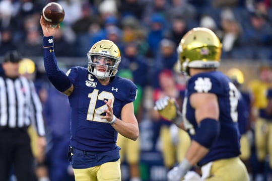 Notre Dame Fighting Irish quarterback Ian Book (12) throws to tight end Cole Kmet (84) in the third quarter against the Boston College Eagles at Notre Dame Stadium.