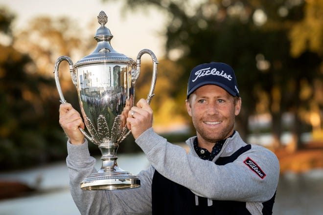 Tyler Duncan holds the trophy after a winning a second hole playoff against Webb Simpson during the final round of the RSM Classic golf tournament in St. Simons Island, Ga., Sunday, Nov., 24, 2019.